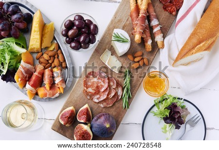Assorted cheese mature cheddar brie camembert and cured meat charcuterie prosciutto wrapped bread sticks with fresh fig, grapes, salad, almonds and white wine - stock photo