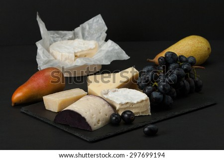 Assorted Cheese On Slate Stone. Grapes, Pears. - stock photo