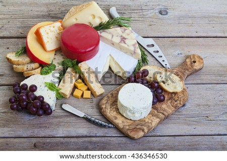 Assorted cheese on wood platter - stock photo