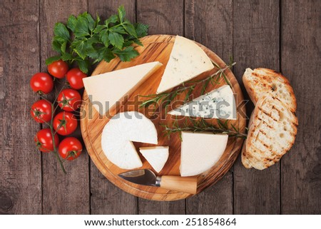 Assorted cheese on wooden platter, rich and healthy snack or breakfast - stock photo