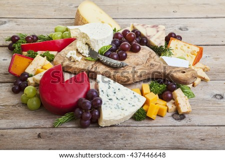 Assorted cheeses on rustic wooden surface - stock photo