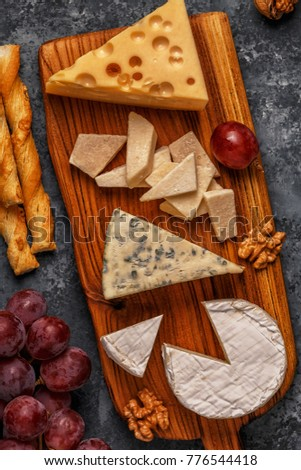 Assorted cheeses on wooden board, top view, copy space.