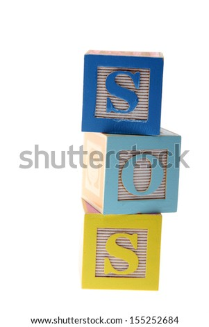 Assorted children's toy letter building blocks against a white background/Childrens alphabet blocks spelling the words SOS - stock photo