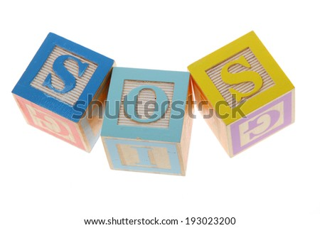 Assorted children toy letter building blocks against a white background/Childrens alphabet blocks spelling the words SOS - stock photo