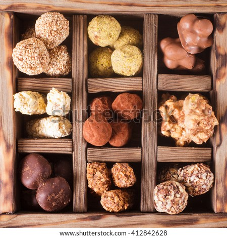 Assorted Chocolate candies in wooden box sells. Luxury handmade sweets - stock photo