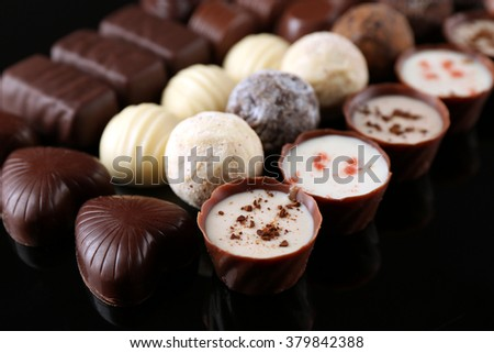 Assorted chocolate candies on black background, close up - stock photo
