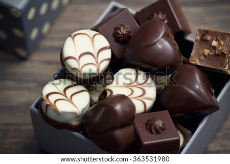 Assorted chocolate pralines on a wooden background - stock photo