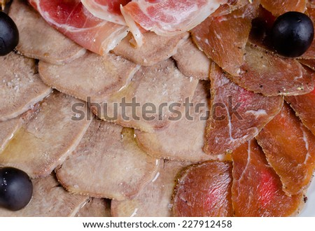 Assorted cold meat platter artistically arranged with varieties of cooked beef, prosciutto ham, lettuce and olives - stock photo