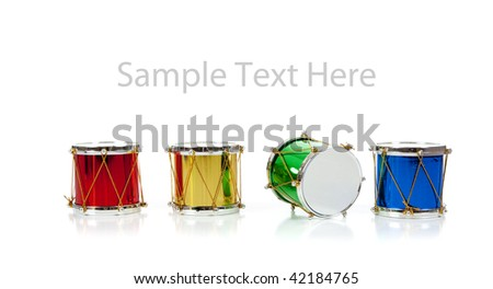 Assorted colored miniature Christmas drums including red, gold, green and blue on  a white background with copy space - stock photo