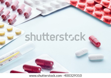 Assorted colorful antipyretics pills and capsules in a Blister packaging thermometer on a light background close up, horizontal, copy space, selective focus, medical concept. - stock photo