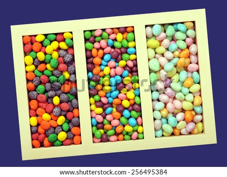 assorted colorful candy in the box isolated on dark blue background - stock photo