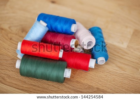 Assorted colorful sewing yarn or thread on reels piled on a wooden countertop conceptual of needlework and handicraft - stock photo