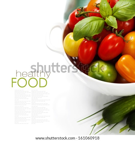 Assorted colorful tomatoes and vegetables in colander on white background - healthy eating concept - stock photo