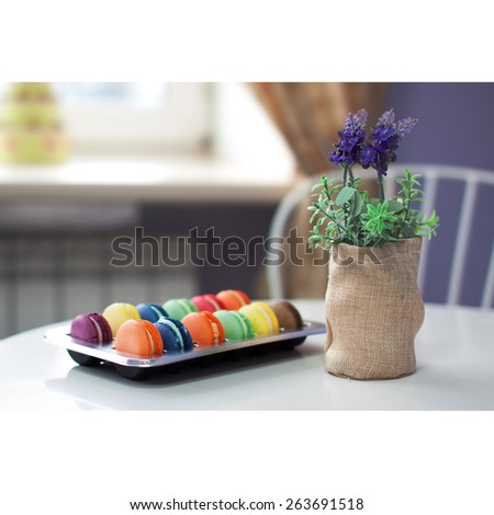 Assorted colors and flavors macaroons french cuisine in a plastic box on a table in cafe next to lavender flowers. Nice creamy bokeh and shallow depth of field. - stock photo