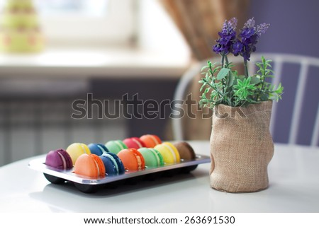 Assorted colors and flavors macaroons in a plastic box on a table in cafe next to lavender flowers. Nice creamy bokeh and shallow depth of field. - stock photo