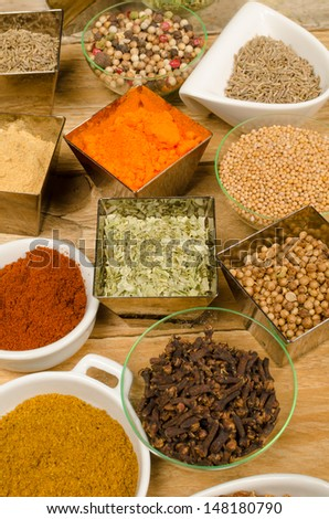 Assorted condiments in small bowls, a food background