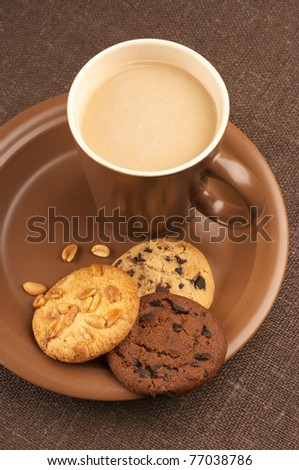 Assorted cookies and brown mug of cappuccino on brown ceramic plate. - stock photo