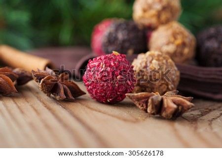 Assorted dark chocolate truffles with dried strawberry pieces and chopped hazelnuts on rustic wooden background, selective focus. Christmas time - stock photo