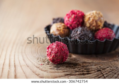 Assorted dark chocolate truffles with dried strawberry pieces and chopped hazelnuts on rustic wooden background, selective focus - stock photo