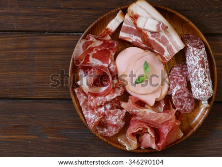 Assorted deli meats - ham, sausage, salami, parma, prosciutto, bacon - stock photo
