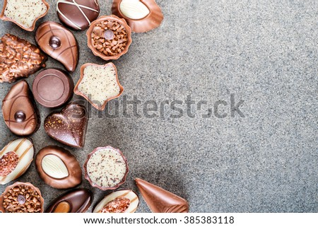 Assorted delicious chocolate pralines background on grey texture, place for text, product photography for patisserie - stock photo