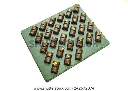 Assorted delicious chocolate pralines with golden crumbs background  - stock photo