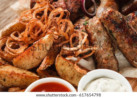 Assorted Delicious Grilled Meat With Fried Potato Wedges Onion Rings And Sauces Close