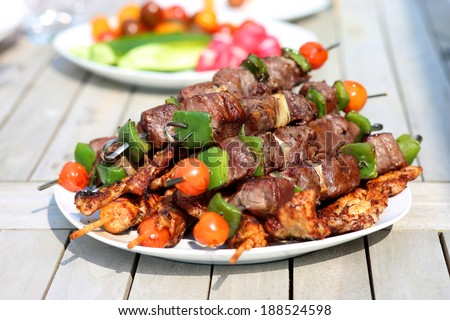 Assorted delicious grilled meat with vegetable on white plate on picnic table for family bbq party - stock photo