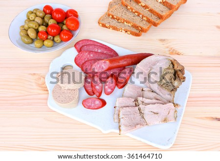 Assorted delicious low fat meats, salamis and sausages on ceramic cutting board - stock photo