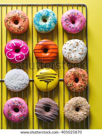 Assorted donuts with different fillings on yellow background - stock photo
