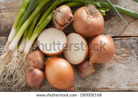 Assorted farm fresh onions on a rustic wooden table with spring onions, brown onions and shallots , with one onion cut in half in the centre of the arrangement, overhead view - stock photo