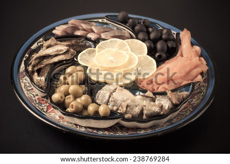 Assorted fish on a plate on a dark background. - stock photo