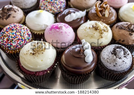 Assorted flavors of decorated cupcakes sitting on silver platter - stock photo