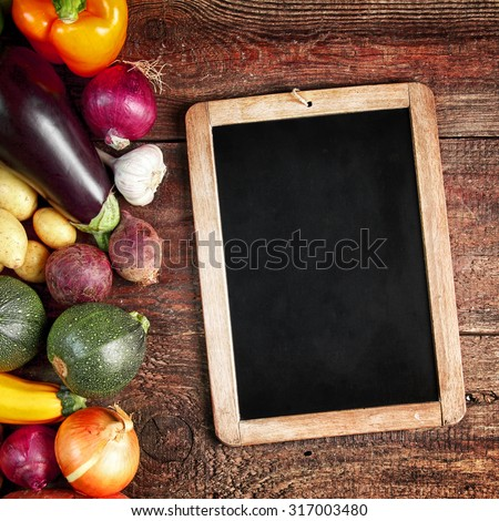 Assorted fresh autumn vegetables with aubergine, squash, onion, sweet pepper, potatoes and marrow with a blank vintage slate on a rustic wooden table, overhead view - stock photo