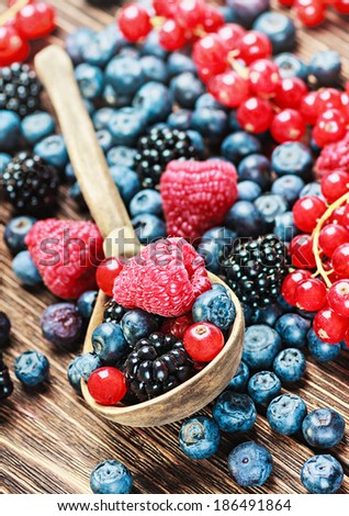 Assorted Fresh berries and old wooden spoon - stock photo