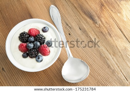 Assorted fresh berries with creamy yogurt including strawberries, blackberries and blueberries, served on a wooden table with copyspace, high angle view - stock photo