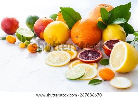Assorted fresh citrus fruits with leaves - stock photo