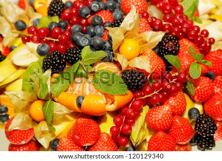 Assorted fresh fruit and berries on a blurred background