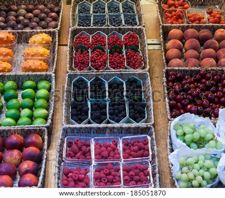 Assorted fresh fruit on display at a farmers market or in a supermarket including berries, peaches, dragon fruit, grapes, cherries and limes - stock photo