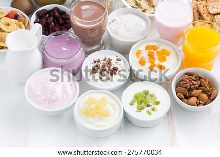 Assorted fresh fruit yoghurts and breakfast ingredients, horizontal, top view - stock photo
