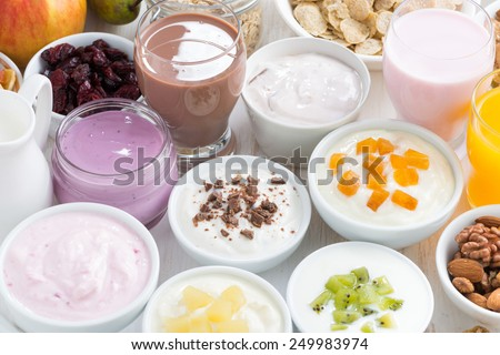 Assorted fresh fruit yoghurts and breakfast ingredients, horizontal, top view, close-up - stock photo