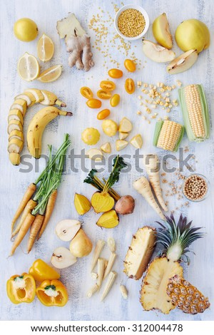 Assorted fresh raw organic produce in yellow hues, pepper capsicum carrot pineapple corn banana parsnip pear soya beans lentils quince, color spectrum collection see more in portfolio flat lay - stock photo