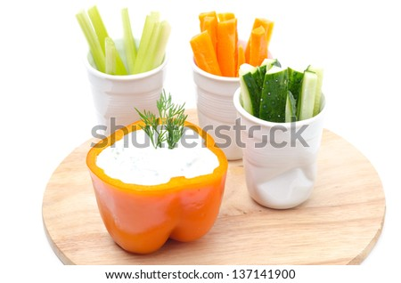 Assorted fresh sliced �¢??�¢??vegetables and yogurt sauce in half of orange pepper on a wooden board, isolated on a white background