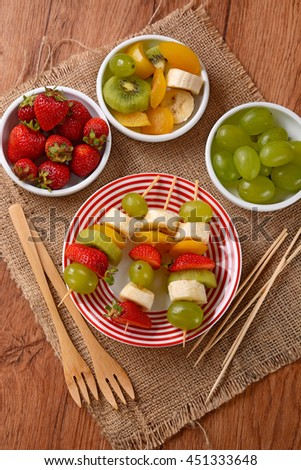 assorted fruit skewers with grapes, kiwi, banana, strawberry and plum