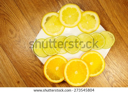 Assorted fruit slices on a saucer on a wooden background - stock photo