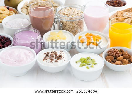 Assorted fruit yoghurts and breakfast ingredients, horizontal - stock photo