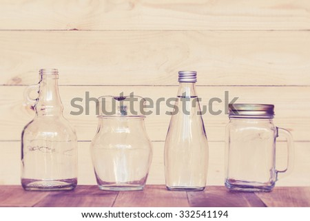 assorted glass bottles on a white washed wooden table. Clear glass bottles and containers of various sizes and shapes. Retro Style. - stock photo
