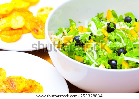 Assorted green leaf lettuce with squid and black olives, close up - stock photo