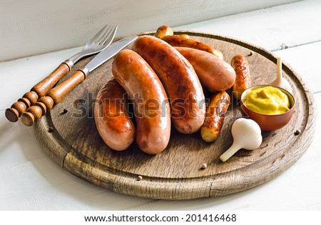 Assorted grilled sausages on rustic round wooden board - stock photo