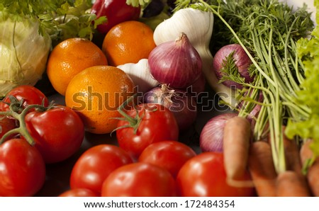 Assorted grocery products including vegetables fruits wine bread dairy and meat  products on the kitchen table vegetables on a kitchen table